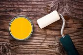 Paint Roller And Color Tin Can On Wooden Background