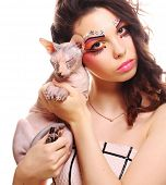 Beautiful woman with creative visage holding Sphynx cat over white background