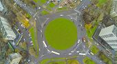 Road roundabout on square with green grass along, view from unmanned quadrocopter.