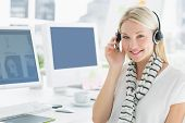 Close-up of a smiling casual young woman with headset sitting by computers in a bright office