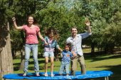 Full length of a happy family jumping high on trampoline in the park