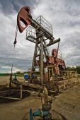 stock photo of nonrenewable  - Oil pumps in the fields vintage rusty colour against moody cloudscape