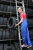 A motivated worker in a tire workshop restocking the goods.
