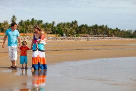 stock photo of family vacations  - Young happy family with two kids on beach vacation - JPG