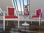 Upholstered antique style wooden armchairs with red upholstery flanking a small table with a vase of