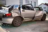 Completely wrecked silver hatchback sedan car with a flattened roof, shattered windows and buckled c