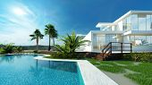 stock photo of blue  - Luxury modern white house with angular walls and large windows overlooking a tropical landscaped garden with palm trees and curving blue swimming pool - JPG