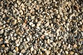 Background of smooth waterworn pebbles in different colors and sizes on a beach or riverbed eroded b