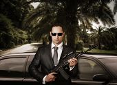 picture of bodyguard  - Confident bodyguard wearing sunglasses while standing against limousine and holding automatic - JPG