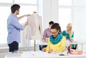 startup, education, fashion and office concept - smiling female drawing sketches and male measuring jacket on mannequin in office