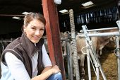 Smiling breeder woman standing in barn