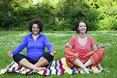 Two Women Meditating In Park
