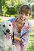 Pretty smiling blonde posing with her labrador in the park on a sunny day