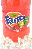Bottle of Fanta drink on ice cubes.