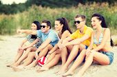 summer, holidays, vacation, happy people concept - group of friends or volleyball team having fun on