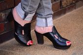 stock photo of spanking  - black spanking and gray jeans female feet with painted red nails - JPG