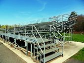 stock photo of bleachers  - Outdoor Gray Metal Bleachers at college athletic field - JPG