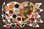 Spice and herb selection on a heart shaped wooden board and in white porcelain dishes.
