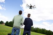 Photography multirotor helicopter being flown by a pilot and photographer