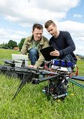 Young male technicians discussing over laptop and digital tablet by UAV helicopter in park