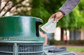 stock photo of garbage bin  - Closeup cropped portrait of someone hand tossing cash dollar bills money hundred dollar bills in trash can isolated outdoors green trees background - JPG