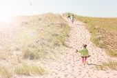Children walking up a dune path to the beach