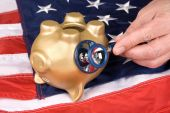 stock photo of inference  - An upside down nearly dead piggy bank on an American flag is being examined for signs of economic and financial life - JPG