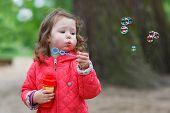 Cute Little Girl Having Fun With Soap Bubbles