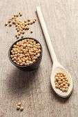 picture of soya beans  - Soya beans in a wooden spoon and a black bowl