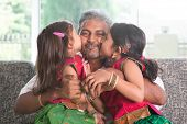 Happy Indian family at home. Two cute Asian girls kissing father, sitting on sofa. Parent and children indoor lifestyle.