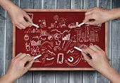Composite image of multiple hands drawing brainstorm with chalk on wooden board