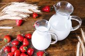 Ripe sweet strawberries and jug with milk on color wooden background
