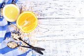 Lemon and orange slices with oatmeal and vintage spoons on color wooden background
