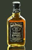 Small bottle of Jack Daniels whiskey isolated on dark background