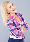Laughing self-assured young blond woman in trendy checked top standing with folded arms smiling at the camera  on grey