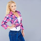 Beautiful trendy busty blond woman wearing a knotted checked top and jeans standing sideways looking over at the camera   three quarter on grey with copyspace