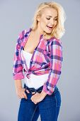 Sexy seductive young blond woman wearing a trendy knotted checked shirt and jeans laughing as she looks flirtatiously to the side