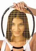 Female looking through strings of tennis racket