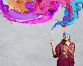 Young woman painter with brush and colorful splashes above