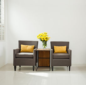 foto of louvers  - Grey armchair in simple setting with yellow flowers  - JPG