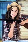 A pretty teen cowgirl taking aim with her rifle.