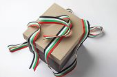 Cut ribbon in UAE flag colors. A gift box from top angle on white background.