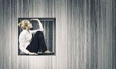Young businesswoman trapped in wooden cube in wall
