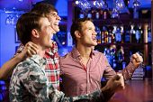 picture of shout  - Three young men at bar watching match and shouting - JPG