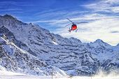 Red Helicopter Flying At Swiss Alps Near Jungfrau Mountain