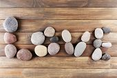 Inscription LOVE made of pebbles on wooden background