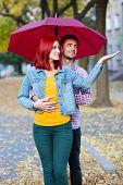 Loving couple under an umbrella in autumn park