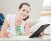Attractive young woman holding 100 euro and tablet device