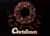 Christmas Wreath And Christmas Wooden Writing On Black.