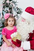 Santa Claus gives a gift to the little girl